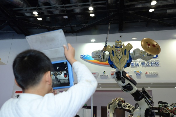 BEIJING, CHINA - NOVEMBER 23: (CHINA OUT) A child takes photos of a Gundam robot at the World Robot Exhibition 2015 at China National Convention Center on November 23, 2015 in Beijing, China. The World Robot Exhibition containing World Forum on Robot, World Robot Exhibition and World Adolescent Robot Contest will be held on Nov 23 to 25 at China National Convention Center in Beijing.  (Photo by ChinaFotoPress/ChinaFotoPress via Getty Images)