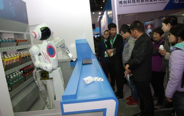 BEIJING, CHINA - NOVEMBER 23:  (CHINA OUT) Visitors order with a robot at the World Robot Exhibition 2015 at China National Convention Center on November 23, 2015 in Beijing, China. The World Robot Exhibition containing World Forum on Robot, World Robot Exhibition and World Adolescent Robot Contest will be held on Nov 23 to 25 at China National Convention Center in Beijing.  (Photo by ChinaFotoPress/ChinaFotoPress via Getty Images)
