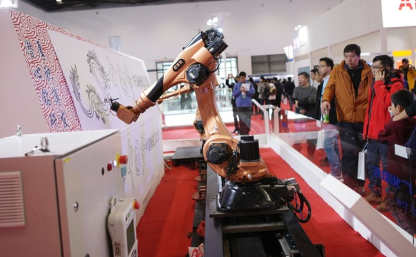 BEIJING, CHINA - NOVEMBER 23:  (CHINA OUT) Visitors look at a robot at the World Robot Exhibition 2015 at China National Convention Center on November 23, 2015 in Beijing, China. The World Robot Exhibition containing World Forum on Robot, World Robot Exhibition and World Adolescent Robot Contest will be held on Nov 23 to 25 at China National Convention Center in Beijing.  (Photo by ChinaFotoPress/ChinaFotoPress via Getty Images)